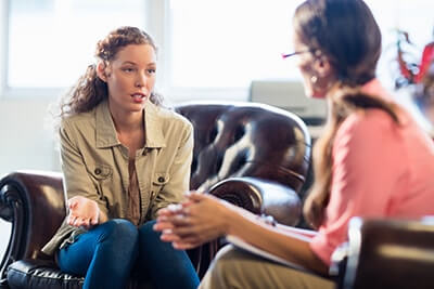 a woman sits with a female counselor during cognitive processing therapy